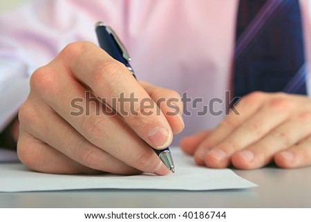Hands of businessman with a pen and paper.
