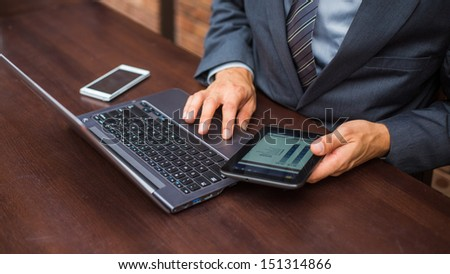 Hands of businessman with laptop,mobile phone and tablet. - stock photo