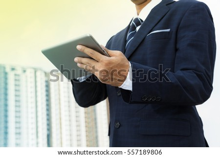 Hands of businessman working on digital tablet outdoor
