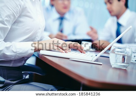 Hands of businesswoman typing on laptop with her colleagues on background