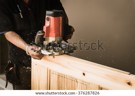 Hands of carpenter with Electronic Plunge Router in the hands on the workbench in carpentry