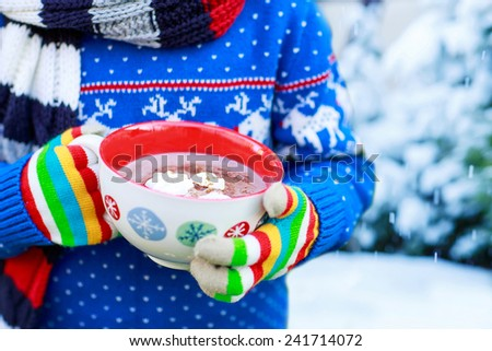 Hands of child holding big cup with snowflakes and hot cocoa and chocolate drink and marshmallows. Kid in winter sweater, long warm scarf and colorful gloves. - stock photo