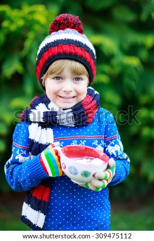 Hands of child holding big cup with snowflakes and hot cocoa and chocolate drink and marshmallows. Kid boy in winter sweater, cap, long warm scarf and colorful gloves. On cold winter day. - stock photo