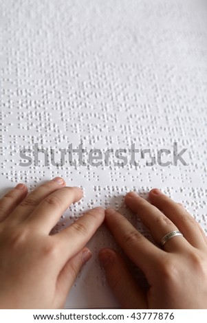 hands of children and Braille print - stock photo