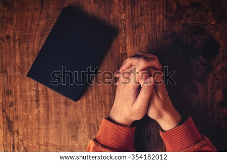 Hands of Christian woman praying with Holy Bible by her side on wooden desk in church, top view,s elective focus - stock photo