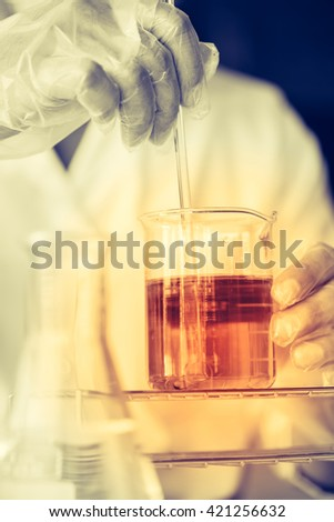 Hands of clinician holding tools during scientific experiment in laboratory - stock photo