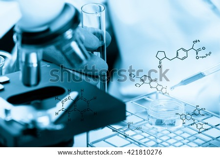 Hands of clinician holding tools during scientific experiment , Researcher is dropping the reagent into test tube, with chemical equations background, in laboratory - stock photo