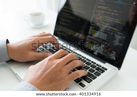 Hands of coder working on new application - stock photo