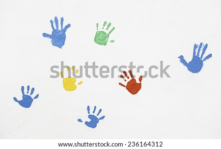 Hands of colors painted on the wall, detail of hands, textured background, shapes and forms - stock photo