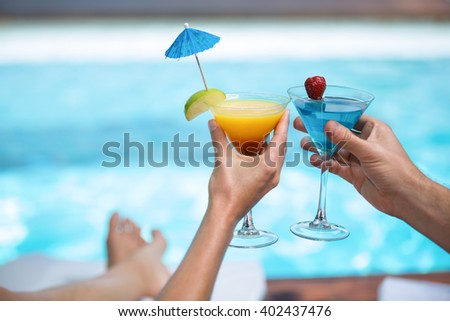 Hands of couple toasting martini glass near pool - stock photo