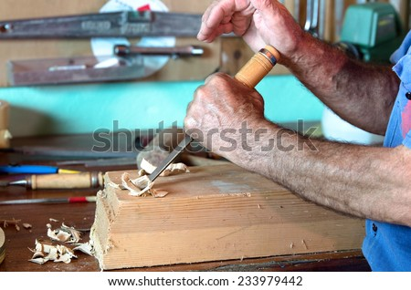 hands of craftsman on workbench modeling manually a decorative figure of wood with carpenters tool in hands / cabinetmaker carving a piece of wood with chisel and using his hand as a hammer - stock photo