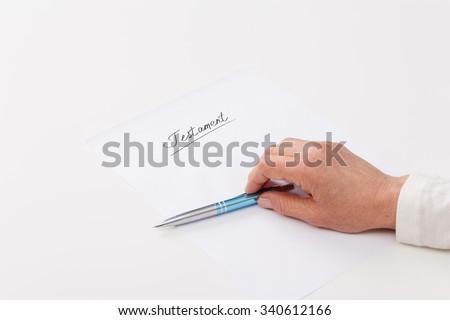 Hands of elderly woman writing ot paper testament  - stock photo