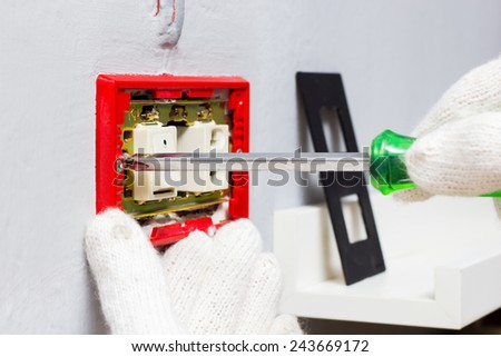 hands of electrician use screwdriver fixing electrical outlet plug on wall - stock photo
