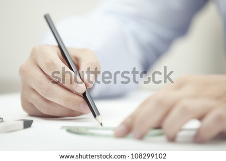 Hands of engineer drawing by pencil - stock photo