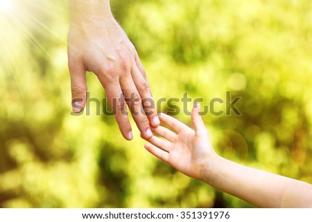 Hands of father and son holding each other