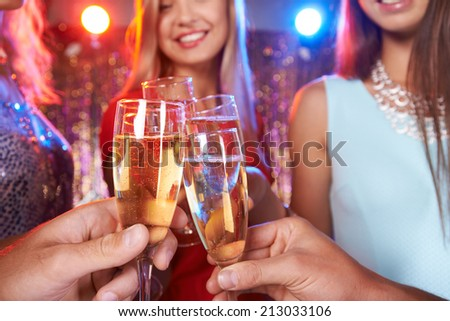 Hands of friends cheering up with champagne at party - stock photo