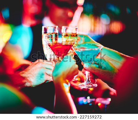 Hands of friends with cocktails making toast at party - stock photo
