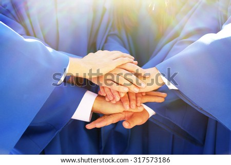 Hands of graduated students in sunshine, close up - stock photo