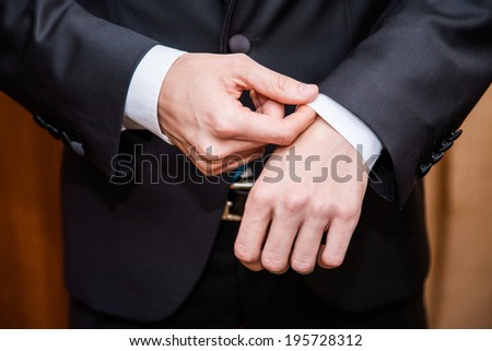 Hands of groom getting ready in suit  - stock photo