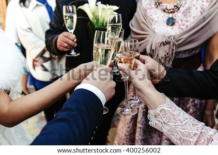 hands of happy people toasting and cheering with glasses of champagne, celebrating wedding, luxury life concept - stock photo