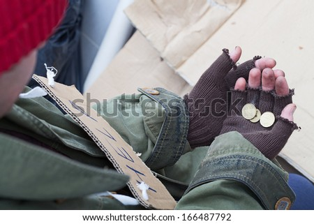 Hands of homeless person holding a few cents - stock photo