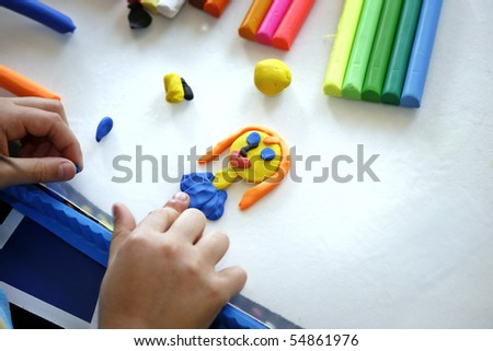 Hands of little girl making doll from colorful clay dough  (plasticine) 1 - stock photo
