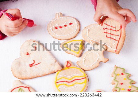 Hands of little girl, who draws on gingerbread cookies - stock photo