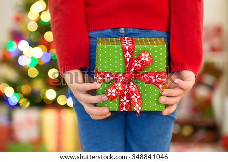 Hands of little girl with Christmas present - stock photo