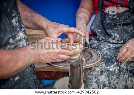 Hands of making clay pot on the pottery wheel. Hands working on pottery wheel. workshop teacher - stock photo