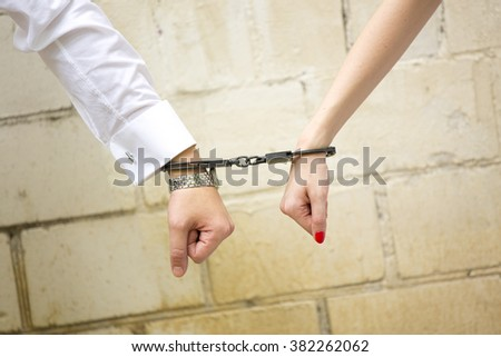 Hands of man and woman/bride and groom in handcuffs