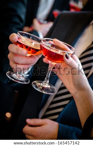 Hands of man and woman cheering with glasses of pink champagne   - stock photo