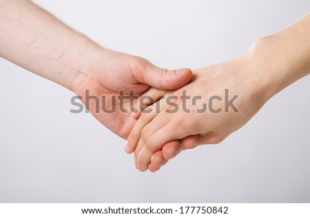 Hands of man and woman holding together on grey background