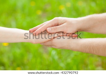 Hands of man and woman holding together on natural green background
