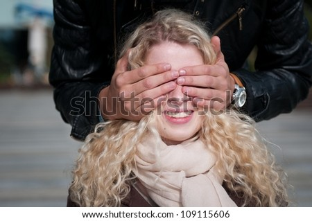 Hands of man covering eyes of young smiling blond woman - outdoor - stock photo