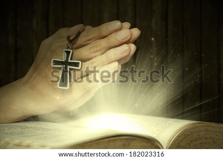 Hands of man holding holy bible and rosary with magical rays coming out from the bible - stock photo