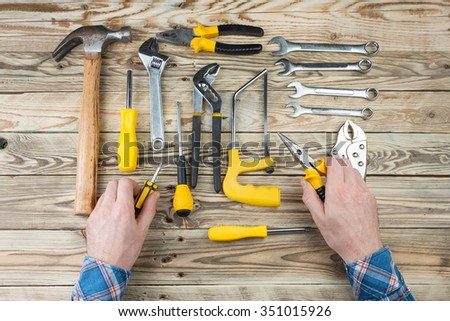 Hands of man in blue plaid shirt holding tools for repair and assembly. Home repair services, calling a master home. Top view