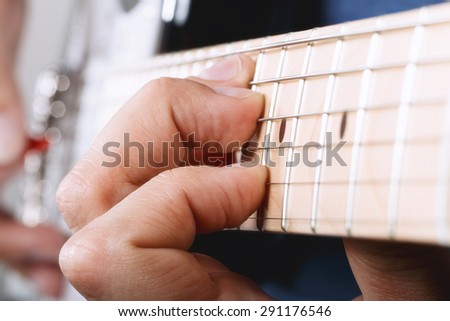 Hands of man playing electric guitar with red pick closeup - stock photo