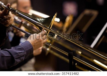 Hands of man playing the trombone in the orchestra - stock photo