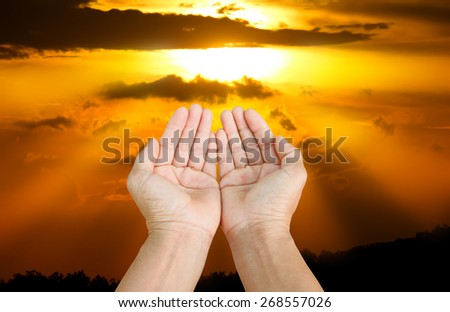 Hands of man praying on a sunset. - stock photo