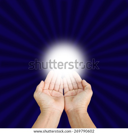 Hands of man praying  on blue background. - stock photo
