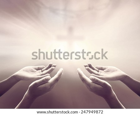 Hands of man praying over blurred crown of thorns and the cross on a sunset. - stock photo