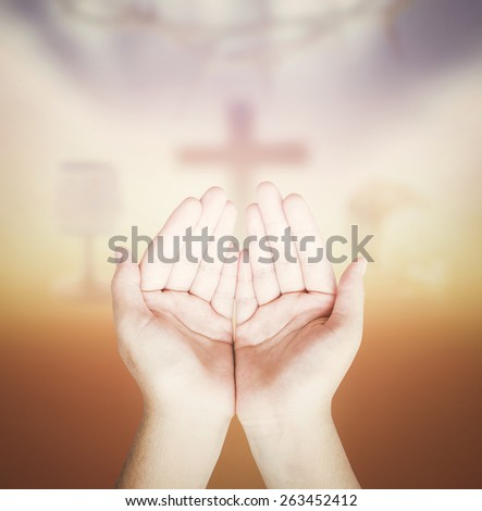 Hands of man praying over blurred glass of wine and Loaf of bread with crown of thorns and the cross on a sunset in eucharist. - stock photo