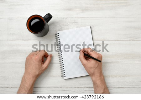 Hands of man writing with a pencil in notebook and cup of coffee standing on wooden table. Business. Science. Study. Intellectual activity.  - stock photo