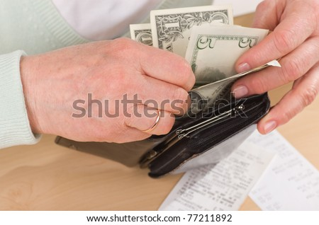 hands of mature woman holding wallet with money