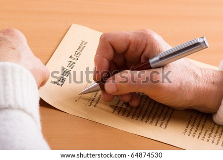 Hands of mature woman signature Last Will sitting on desk - stock photo