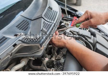 Hands of mechanic working in auto repair shop - stock photo