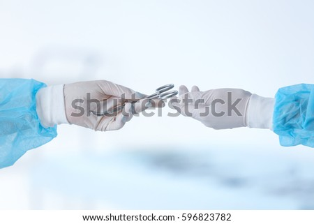 Hands of medical assistant and surgeon with special medical instrument on light blurred background