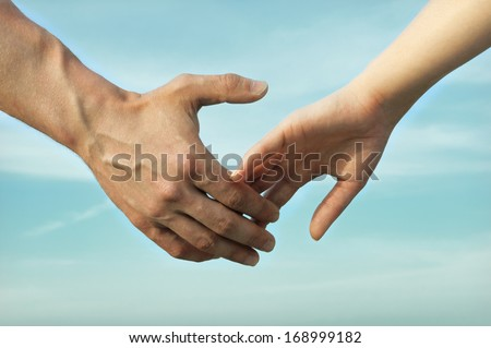 Hands of Men and Women on Blue Sky Background - stock photo
