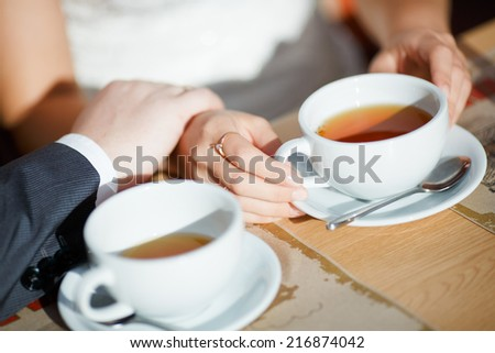 Hands of men and women who poured tea. Close-up of beautiful white cups which poured a drink of golden color. Men's hands gently holding women's hands.