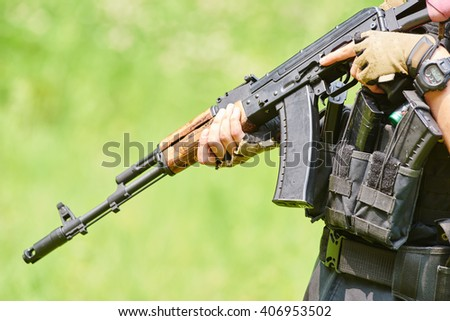 Hands of military soldier with assault rifle  - stock photo
